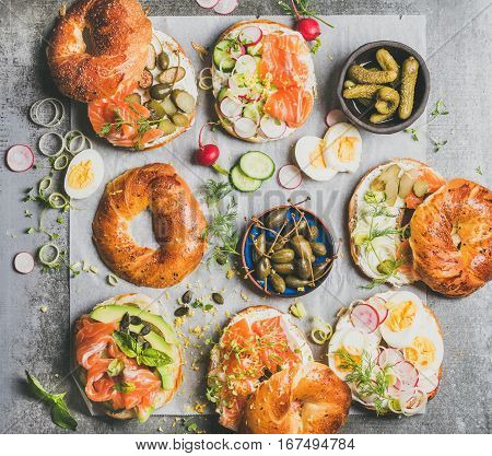Variety of bagels with smoked salmon, eggs, radish, avocado, cucumber, greens, cream cheese, pickle for breakfast, healthy lunch or party over grey concrete background, top view. Takeaway food concept