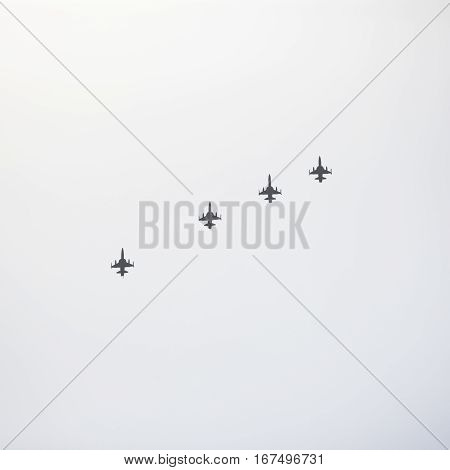 Silhouette of four jets directly above in formation