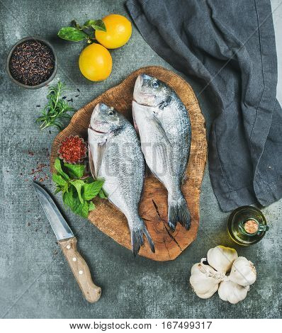 Fresh uncooked sea bream or dorado fish with lemon, herbs, olive oil, garlic and spices in bowls on rustic wooden board over grey concrete background, top view. Healthy, dieting, clean eating concept