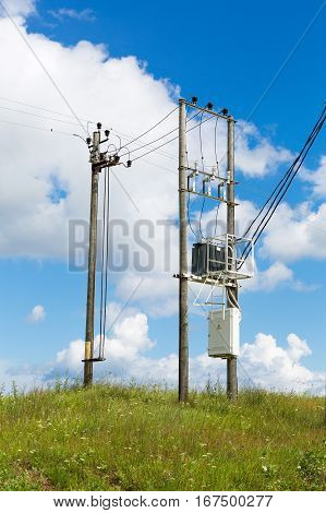Transformers of an electrical post with power lines cables against bright blue sky. Transformer with the electricity poles in the field.