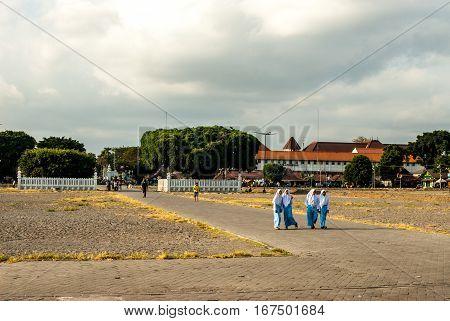 Yogyakarta, Indonesia - September 2, 2015: Young Muslimas walking in blue across Kraton square