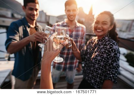 Happy young people toasting drinks at rooftop party. Young friends hanging out and enjoying with drinks. POV shot.