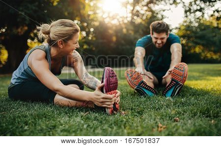Young Caucasian Couple Exercising In Park