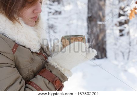 Young woman in winter coat and white fluffy mittens holds pottery cup in her hands at the background of snowy forest. Shallow dof. Focus on cup.
