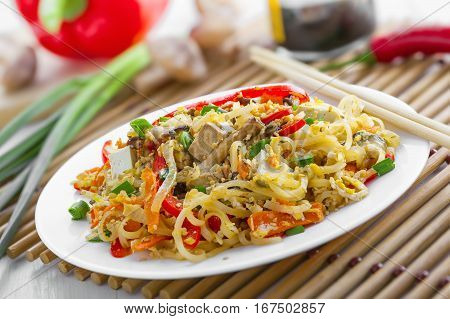 Plate of traditional Asian food. Rice noodles with tofu vegetables and shiitake mushrooms. Oriental cuisine meal.