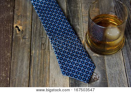 whiskey drink in glass with ice ball and man's blue tie on rustic wood