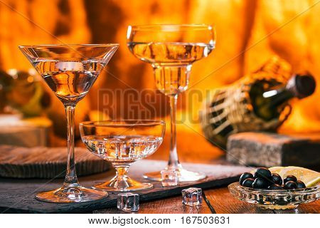 Three wine glasses, icecubes and olives. Fire on the background