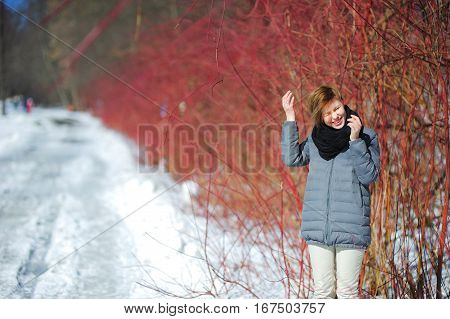 Portrait of happy smiling beautiful girl with blond hair in winter forest near the road. A woman without a hat in warm clothes she squints from the bright light.