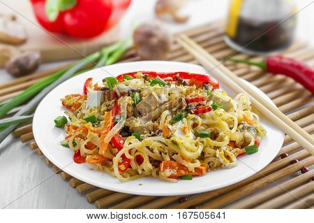 Plate of stirred rice noodles with tofu vegetables and shiitake on a table. Traditional Asian cuisine meal.