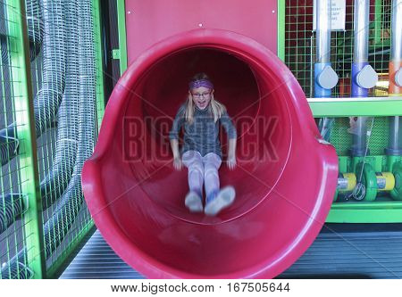 LAS VEGAS, NEVADA, DECEMBER 29. The Discovery Children's Museum on December 29, 2016, in Las Vegas, Nevada. A Girl Rides Down a Big Red Slippery Slide Tube at the Discovery Children's Museum in Las Vegas Nevada.