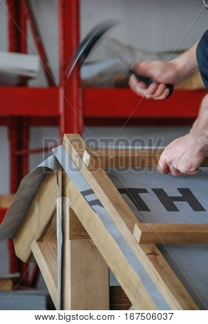 Roofer putting nails in the wooden battens with a hammer