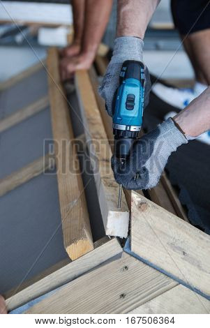 Roofer screwing down the wooden battens, close up view
