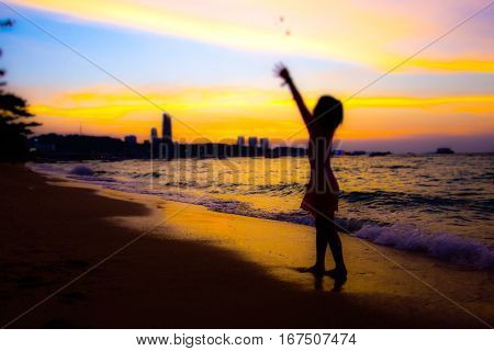 Asian girl playing sand cast on the beach nice shot in sunset time at Pattaya Thailand Silhouette photo and focus select at sand wave around are blur concept funny alone.