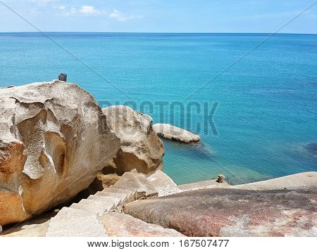 Rocks and blue sea. Staircase with stone steps down between the rocks to the sea