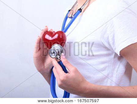 Female medicine doctor hold in hands red toy heart and stethoscope head. Cardio therapeutist, student education, physician make cardiac physical, heart rate measure, arrhythmia concept