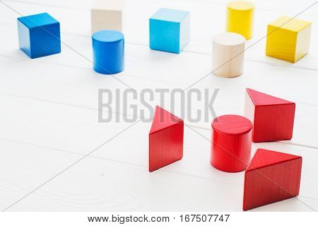 Colorful wooden blocks on white wooden background. Creativity toys. Children's building blocks. Geometric shapes - cube triangular prism cylinder. The concept of logical thinking.
