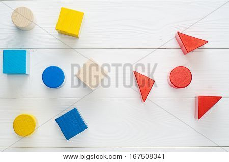 Colorful wooden blocks on white background top view flat lay. Children's creativity toys. Geometric shapes - cube triangular prism cylinder. The concept of logical thinking.