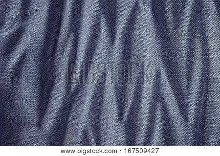 Close Up Picture Of Wrinkly Blue Jeans Fabric Background.