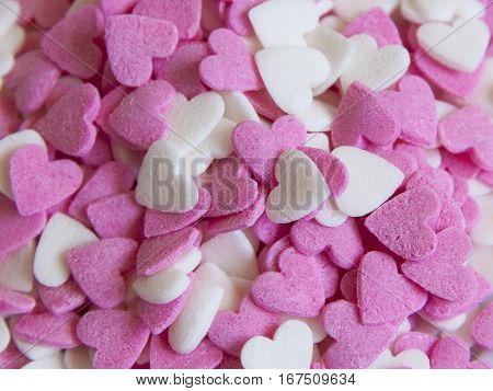 Pequeños corazones rosas y blancos de azúcar