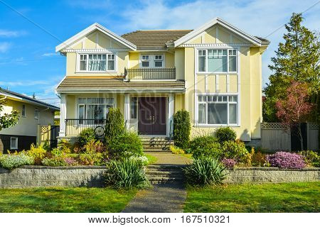 Big family house with landscaped front yard terrace on blue sky background