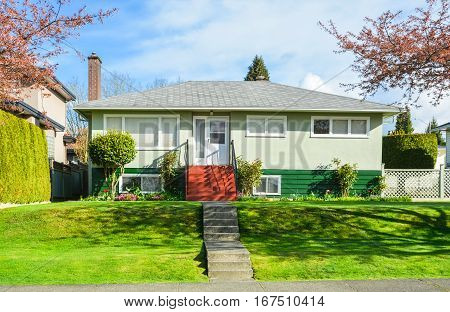 Average family house in Canada. Residential house with landscaped front yard on blue sky background