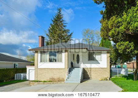 Modest family house with garage in Canada. Residential house with concrete paved front yard on blue sky background