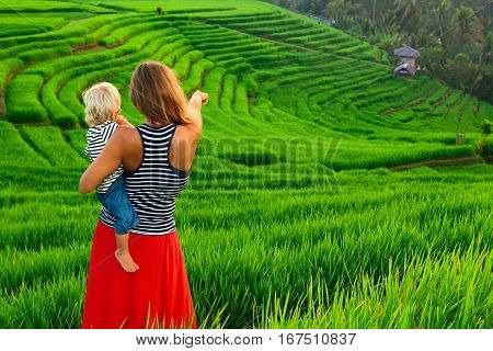 Beautiful view of Balinese traditional fields. Nature walk in green rice terrace. Happy mother hold happy little baby traveler. Travel adventure with child family summer vacation in Bali Indonesia