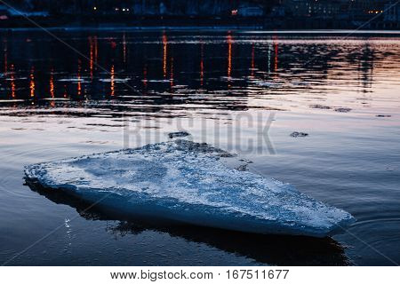 Blue melting ice floe floating in the river in the city