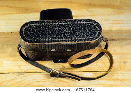 Old vintage soviet rangefinder camera in a leather case on a wooden table