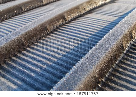 Frost crystals on corrugated metal roof panels close up