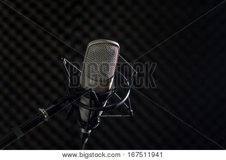 Microphone and audio console in holder isolated on dark background in recording studio