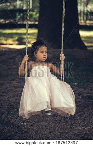 little girl in a pink ballroom dress on nature