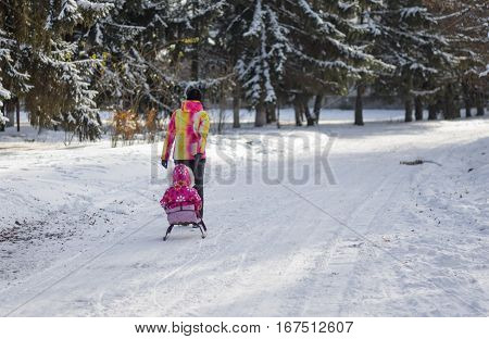 DNEPR UKRAINE - DECEMBER 04 2016:Mother walking on an empty snowy street driving sledge with kid in Dnepr Ukraine, at December 04 2016