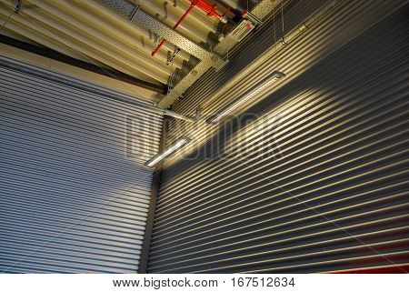 Corrugated sheet metal cladding wall and ceiling illuminated by interior lighting