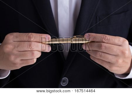 A man in black casual suit giving a gold fountain pen for sign the contract in formal way