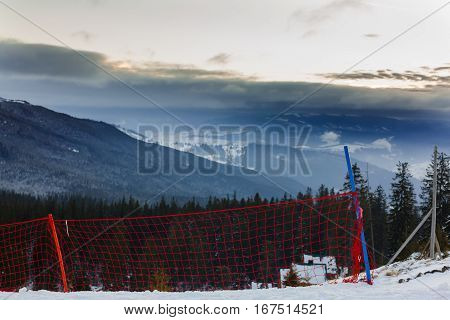 defense net on mountain ski resort in bright winter day Net on the snow in the mountains