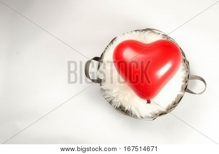 Red balloon heart in a basket with lambskin, placed right, on white background