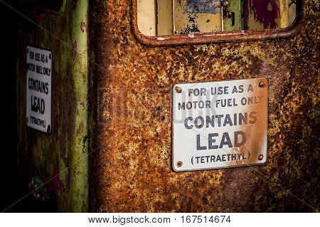 Abandoned gas pump with a rust and signs