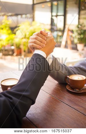 Two business man arm wresting while having coffee at the coffee shop