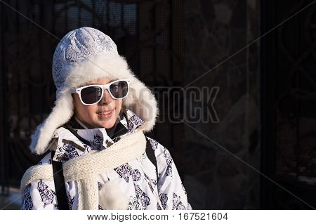 Portrait of a stylish little girl on the walking with winter clothes and sunglasses.Fashionable child. Caucasian stylish little girl in winter clothes walking outdoor.
