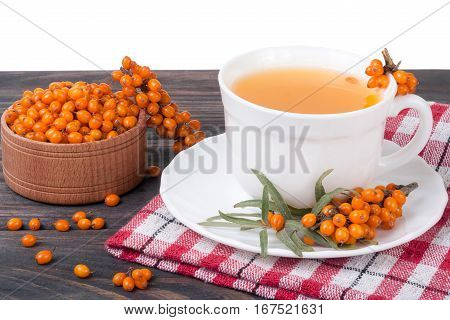 Tea of sea-buckthorn berries on wooden table isolated on white background.