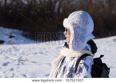 Portrait of a stylish little girl on the walking with winter clothes and sunglasses.Fashionable child. Caucasian stylish little girl in winter clothes walking outdoor. Side view