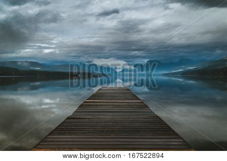Dock overlooking a calm overcast lake in Montana.