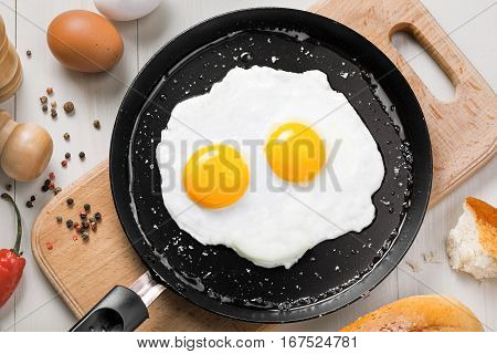 Delicious healthy simple breakfast meal made of eggs on a frying pan ready. Traditional homemade quick breakfast. International cuisine food. Top view.