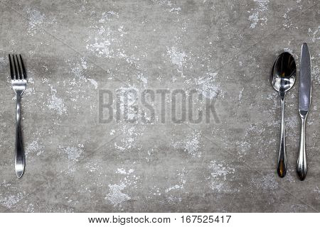 Stone table with a fork and knife,a Good background for creating restaurant menus, cafes bars.The style of grunge.