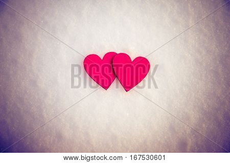Two red hearts lie on the snow