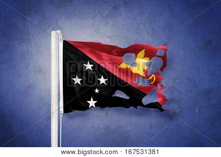 Torn flag of Papua New Guinea flying against grunge background.