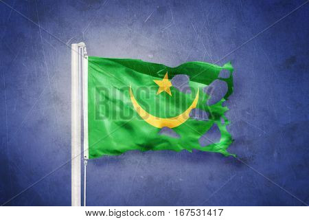 Torn flag of Mauritania flying against grunge background.