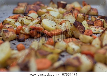 Roasted potatoes and carrots on a baking stone.