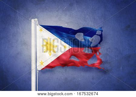 Torn flag of Philippines flying against grunge background.